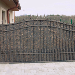 A wrought iron gate with metal