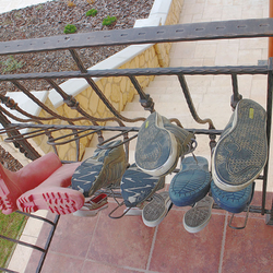 A wrought-iron railing by the entrance of a family house with forged shoe-rack