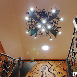 A wrought iron bat above a gallery - an eye-catching chandelier